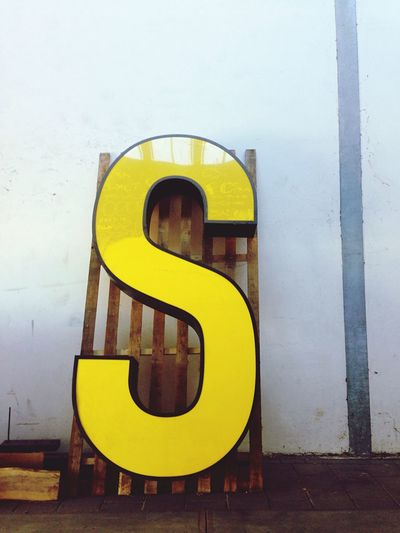 Low angle view of letter s against sky