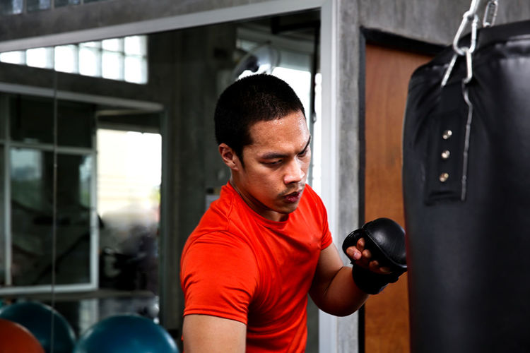 Young man practicing boxing in gym