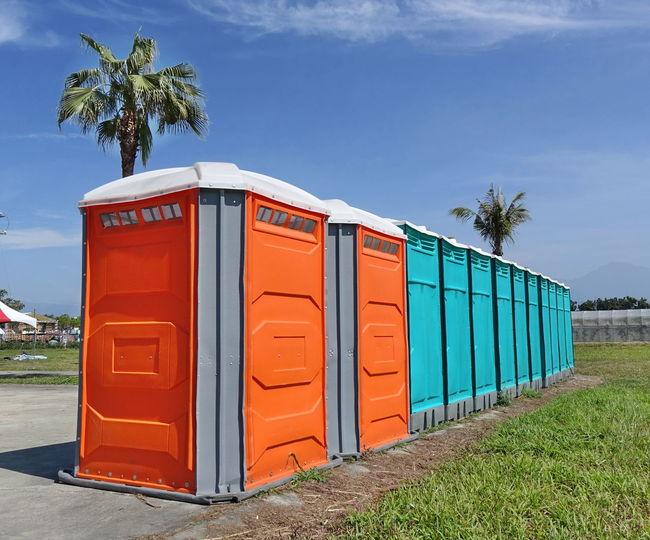 Portable toilets under a blue sky Green Color Hygiene Perspective Toilet Urinal Bathroom Blue Sky Day Orange Color Outdoors Palm Tree Plastic Portable Toilets Portapotty Sanitation Sunlight