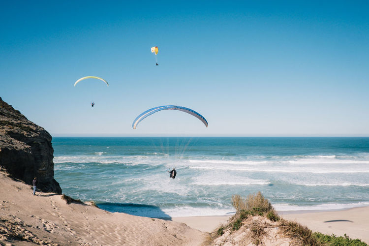 People paragliding over sea against clear blue sky