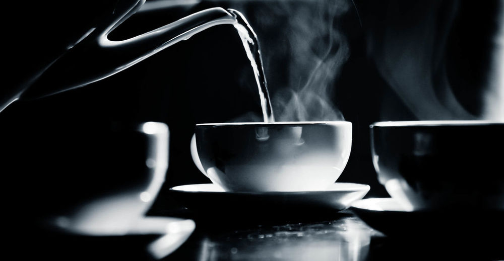 Pouring boiling water into teacup