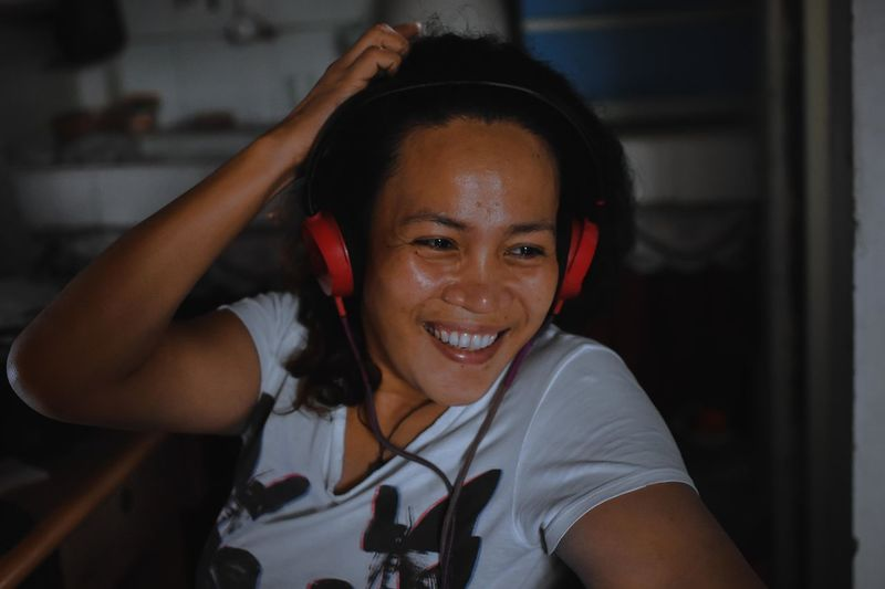 Smiling woman looking away while wearing headphones