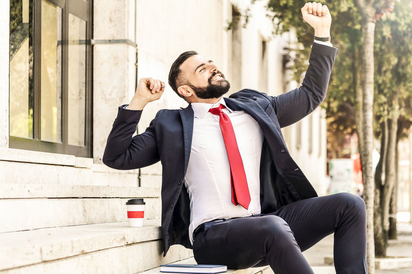Model: Roberto Materiale Architecture Arms Raised Beard Built Structure Business Business Person City Day Focus On Foreground Formalwear Human Arm Males  Men One Person Outdoors Real People Sitting Suit Three Quarter Length Well-dressed Young Adult Young Men