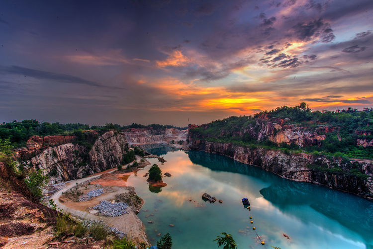 The Long Exposure blue Lake At Abandoned quarry during sunset Arrival Beauty City Cityscape Cultures Grass Igniting Landscape Mountain Nature Night No People Outdoors Reflection Lake River Scenics Sky Social Issues Sunset Tourism Travel Tree Urban Skyline Village Water