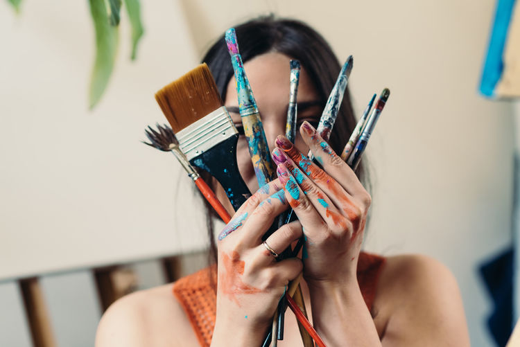 Portrait of woman holding paintbrushes