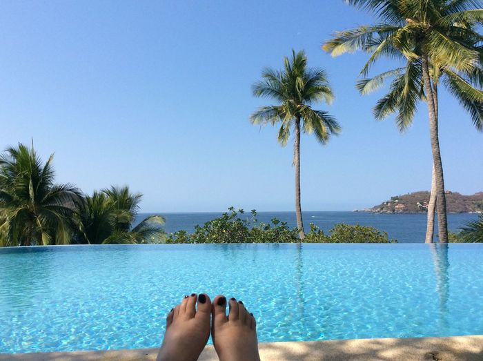 Low section of woman against infinity pool and sea