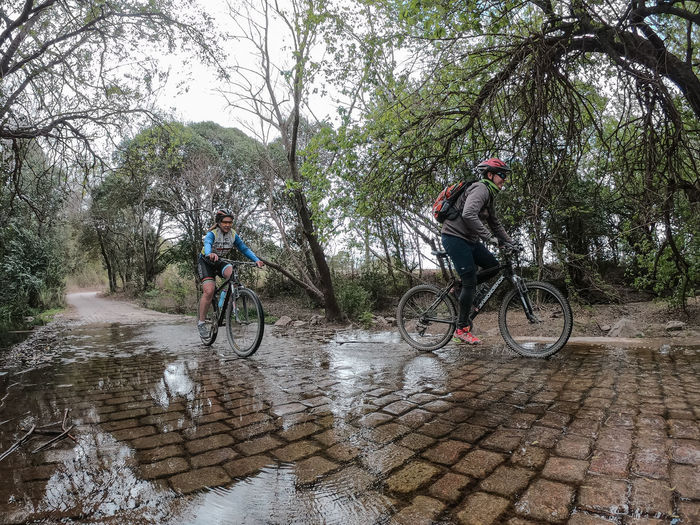 People riding bicycle on rainy day