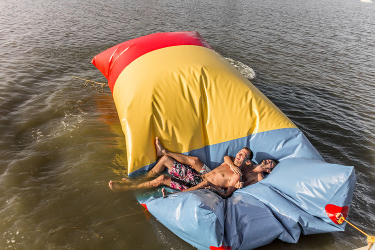 High angle view of happy friends lying on inflatable equipment floating in lake