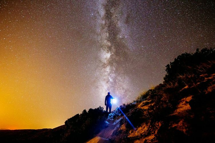 Low angle view of silhouette man with flashlight standing on mountain against star field at night