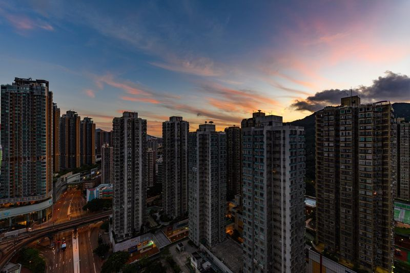 Buildings against sky during sunset in city