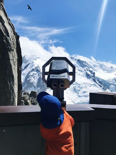 Rear view of boy looking through coin-operated binoculars against snowcapped mountains