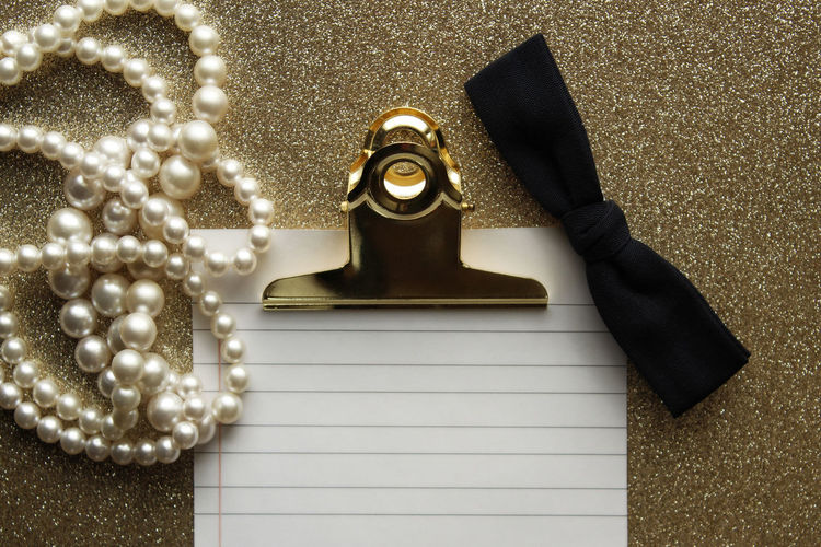 Directly above shot of paper with clip and pearl necklace