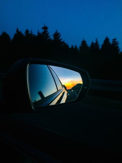 Reflection of car on side-view mirror at sunset