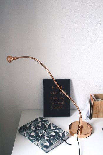 Diary And Table Lamp Against Wall