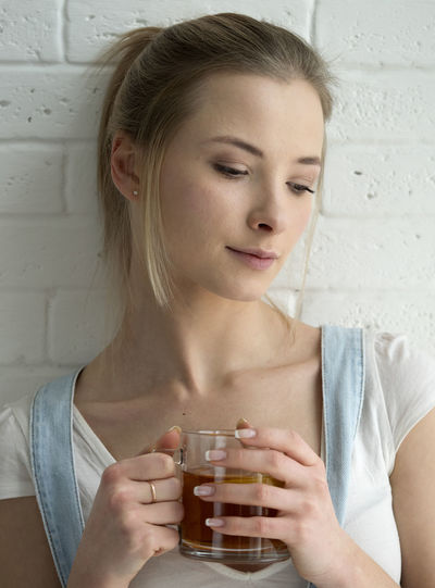 beauty young caucasian woman in blue denim overalls and a white T-shirt drinking tea front of brick wall Adult Adults Only Beauty Blue Brick Caucasian Day Denim Drinking Indoors  One Person One Woman Only One Young Woman Only Only Women Overalls People T-shirt Tea Wall White Woman Young Young Adult Young Women