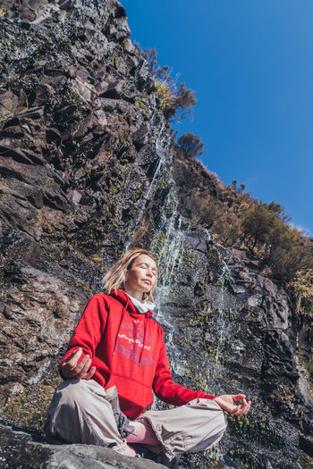 Calm Meditation Meditation Place Peace Reflection SPIRITUAL HEALING Spirituality Beauty In Nature Blond Hair Casual Clothing Day Hiking Inner Peace Leisure Activity Mountain Nature One Person Outdoors Real People Rock - Object Sitting Sky Smiling Spiritual Waterfall