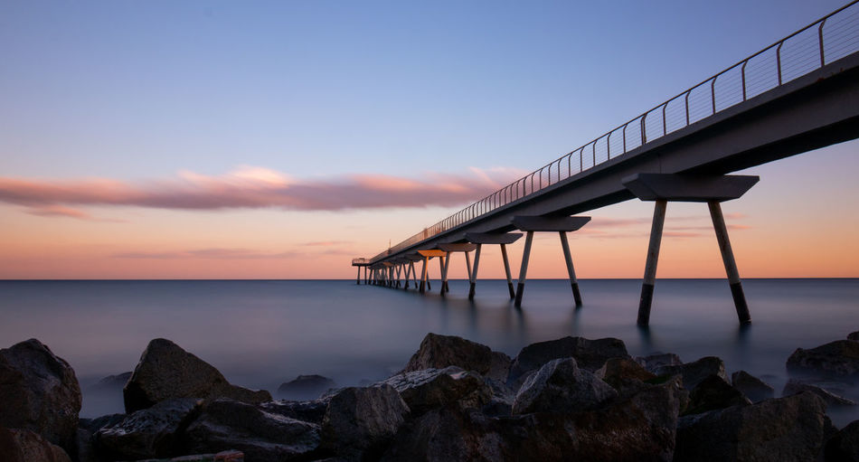 Sky Water Sea Sunset Scenics - Nature Beauty In Nature Built Structure Rock Architecture Horizon Over Water Nature Rock - Object Cloud - Sky Horizon Tranquil Scene Solid Tranquility Bridge Beach No People Bridge - Man Made Structure Outdoors Pont Del Petroli Pont Del Petroli, Badalona, Spain Long Exposure Clouds Calm Place