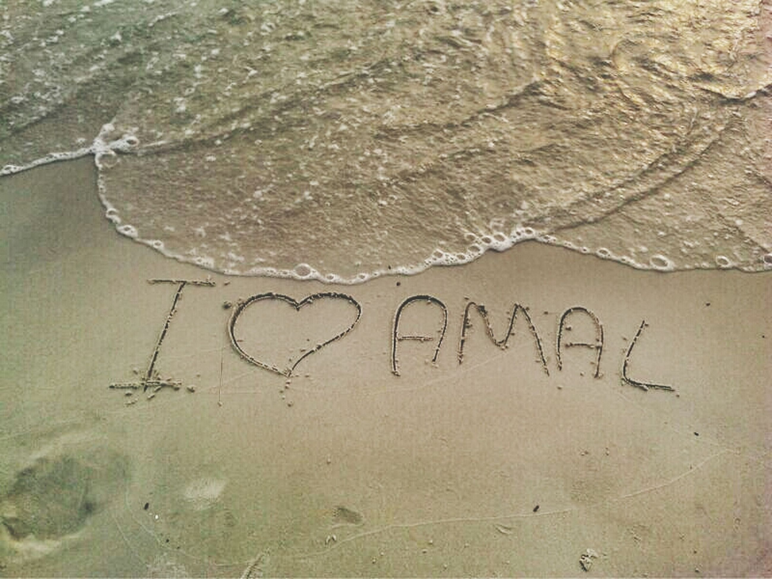 text, western script, high angle view, communication, sand, beach, heart shape, day, water, love, close-up, outdoors, capital letter, message, no people, nature, creativity, footprint, art, art and craft
