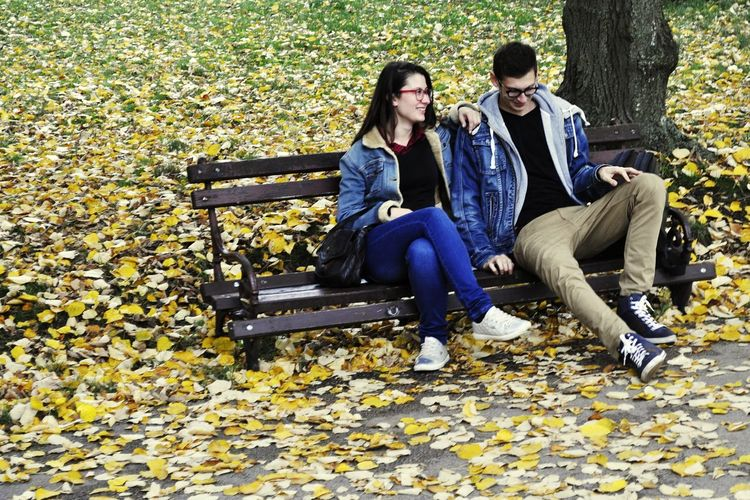 Couple sitting in park during autumn