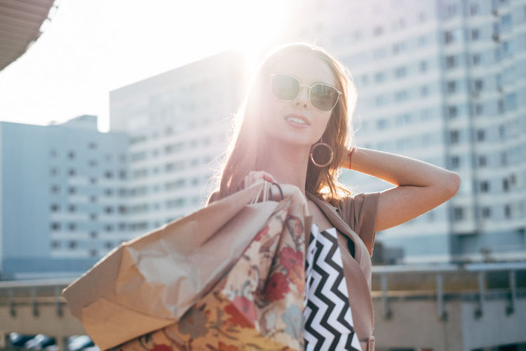 Stylish woman with shopping bags City Building Exterior Shopping Stylish Black Friday Women Young Women One Person Glasses Sunglasses Portrait Fashion Beautiful Woman Standing City Life Sunlight Lifestyles Hairstyle Lens Flare Outdoors Hair Well Dressed Skyscraper Street Fashion