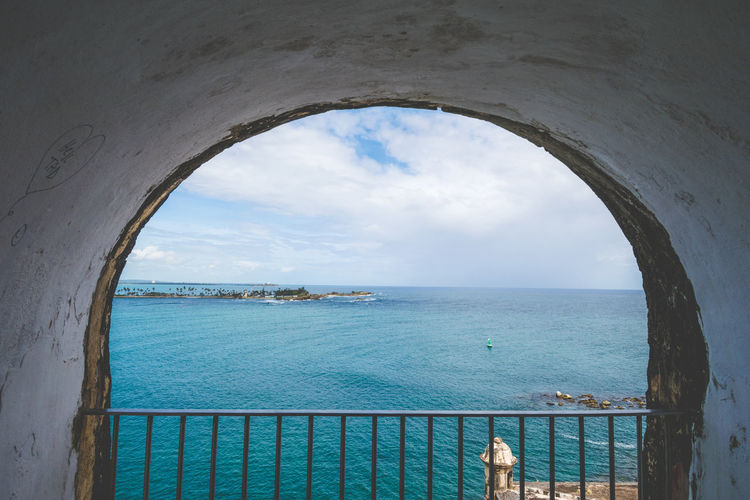 Scenic view of sea against sky seen through railing