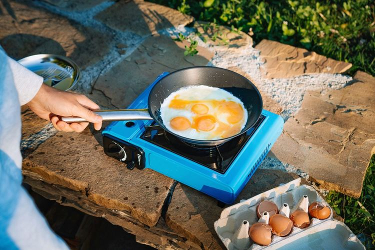 High angle view of man preparing omelet food on camping stove