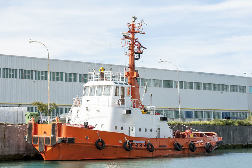 Orange tug moored in port waiting to tow ships. Harbor Moored Boats Beauty In Nature Cloud - Sky Commercial Dock Cruise Ship Day Freight Transportation Harbor Mode Of Transport Moored Nautical Vessel No People Outdoors Sailing Ship Sea Ship Shipyard Shipyardlife Sky Transportation Tug