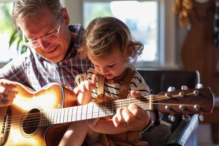 Grandfather teaching guitar to daughter