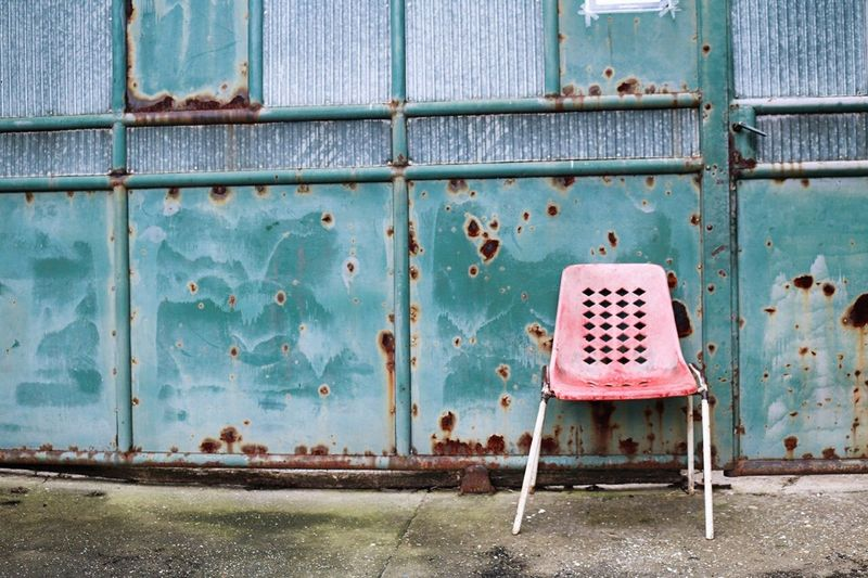 Empty chair against rusty wall