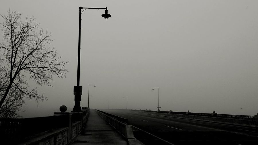 Street light on bridge against sky during foggy weather
