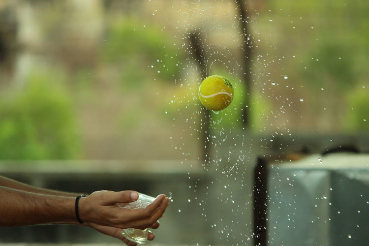 Close-up of hands holding plastic by tennis ball amidst water drops