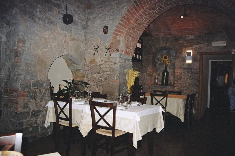 A lovely table is set and ready for diners and wine lovers in this old stone and brick restaurant in Montalcino, Italy, a Tuscan town famous for its Brunello wine. Arch Architecture Bricks Chair Dining Empty Enoteca Home Interior Indoors  Interior Italian Italian Food Italy Montalcino. Old Restaurant Stone Stone Wall Table Taverna Tuscany Wall Wall - Building Feature Wine