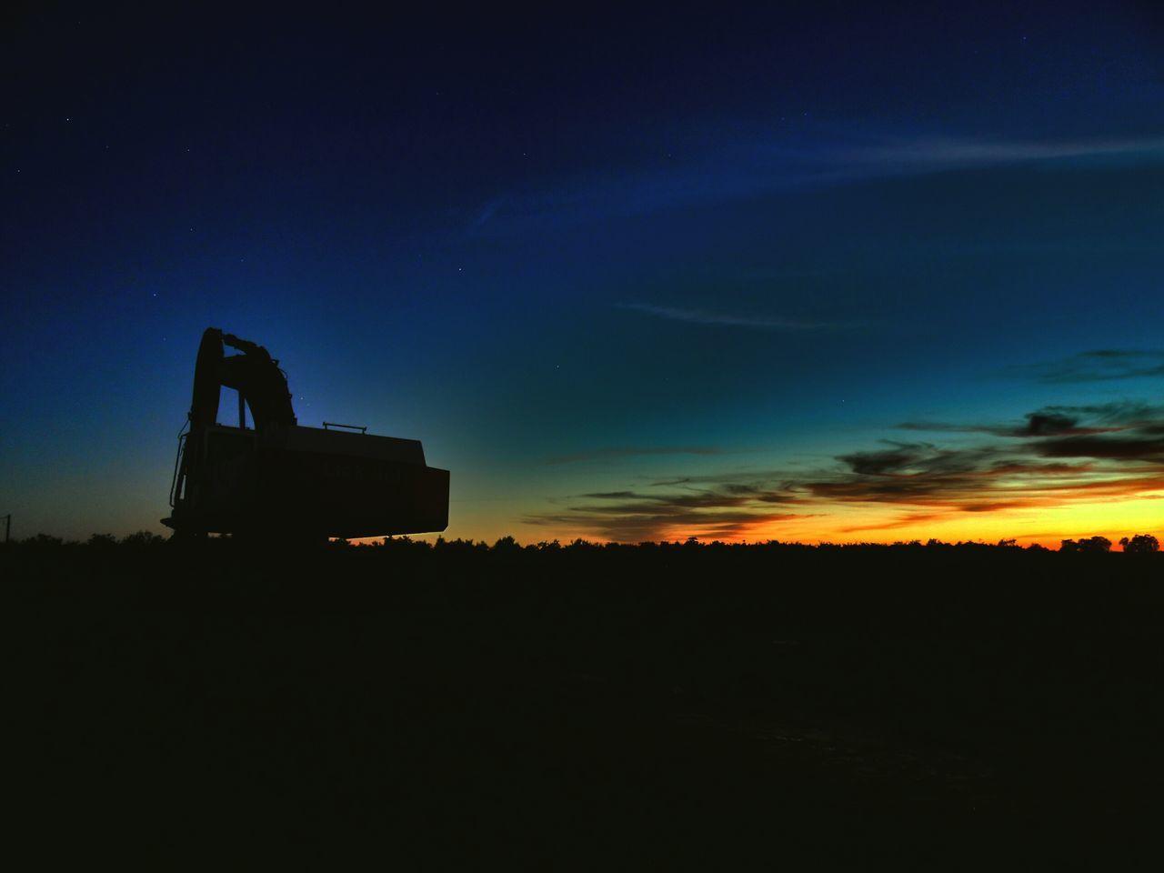 Silhouette Bulldozer On Landscape Against Sky