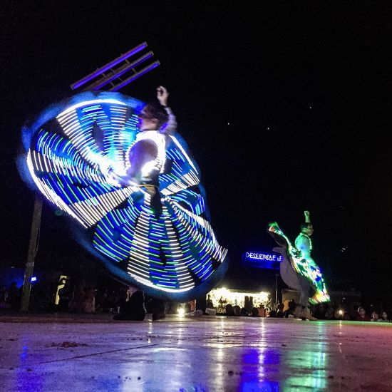 Illuminated ferris wheel against blue sky