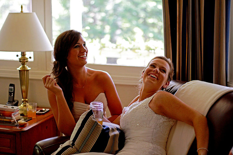 Happy Bride With Maid Sitting On Sofa At Home