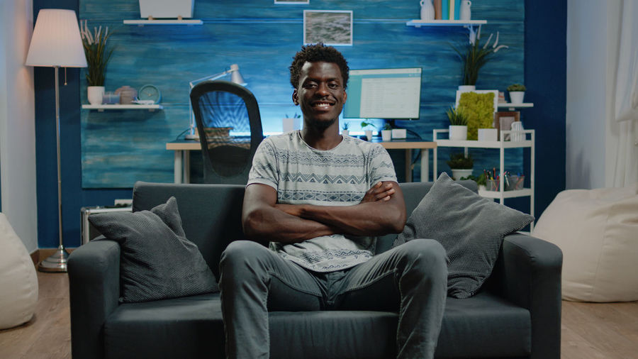 Portrait of young man sitting on sofa