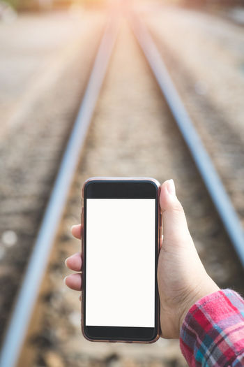woman's hand holding and using smartphone, black screen with blur railway background. subject is blur. Wireless Technology Communication Human Hand Technology Connection Holding Hand One Person Human Body Part Smart Phone Mobile Phone Rail Transportation Screen Portable Information Device Track Railroad Track Transportation Touch Screen Focus On Foreground Outdoors Finger
