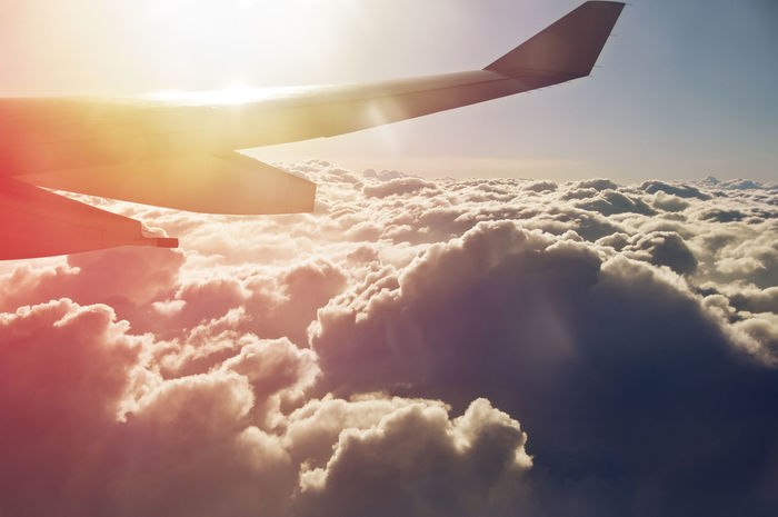 Travel background of passenger view from the plane flying above the clouds on sunset, sunrise. Sky Travel Destinations Sunset Sunlight Backgrounds Plane Cloudscape Above Flight Flying Holiday Destination Trip Vacations Air Transportation Airplane Cloud - Sky Industry Transportation Colorful Passenger View