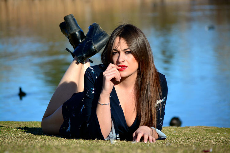 Young woman sitting on grass by lake
