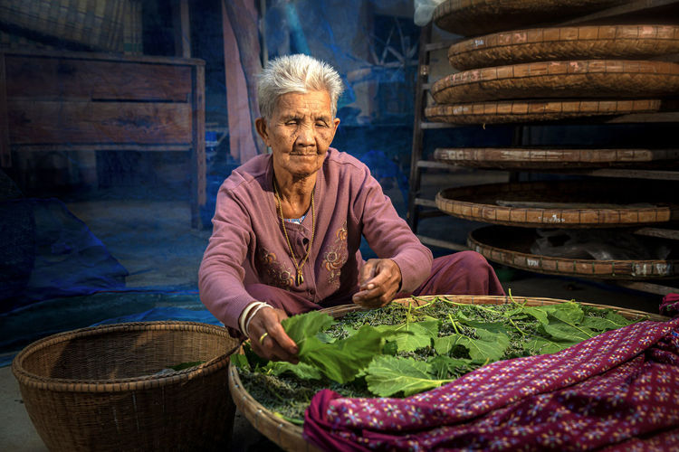 Senior woman with vegetables in wicker basket