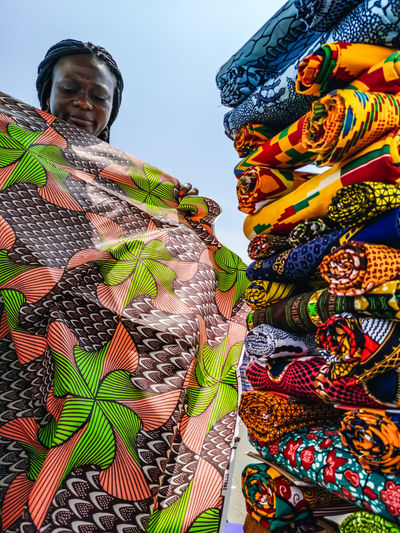 Ghana woman looking at various fabrics in accra market located in ghana west africa.