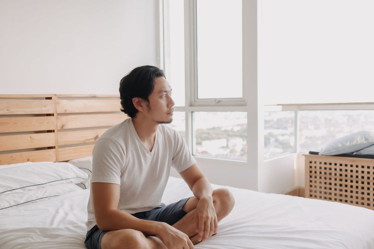 Young man sitting on bed