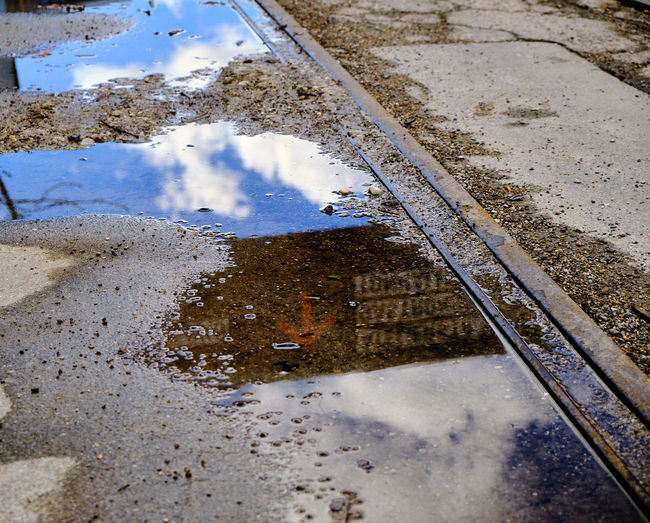 Reflection of clouds in puddle on road during rainy season