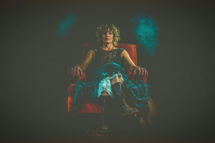 Digital composite image of woman sitting against black background
