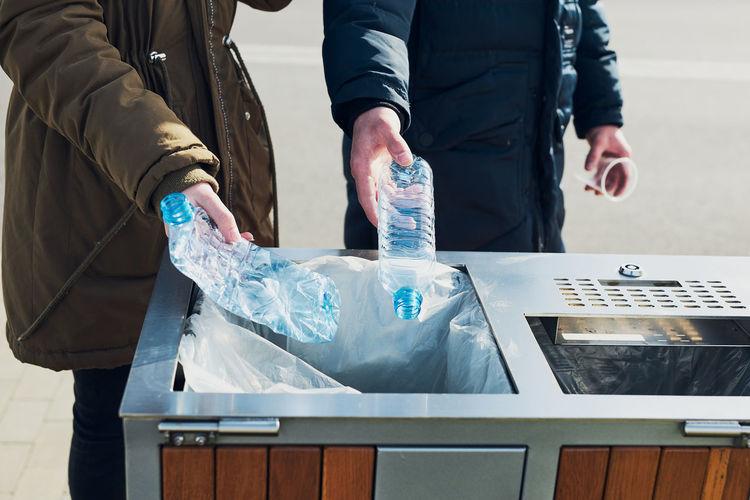 Midsection of people throwing bottles in garbage bin