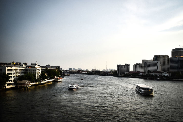 View of river and buildings against clear sky