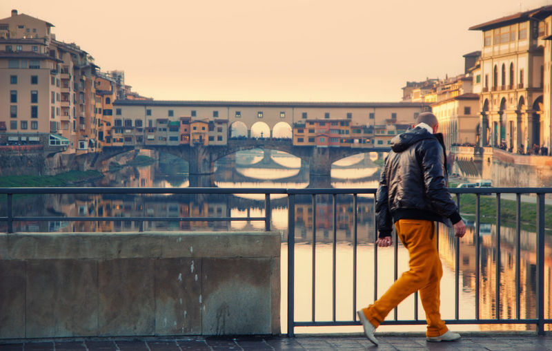 Man Walking On Footbridge Over River Against Sky