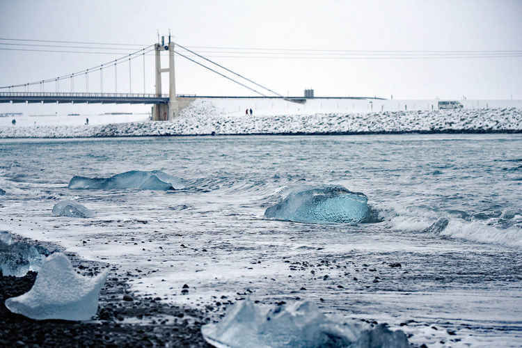 Bridge over sea against sky during winter