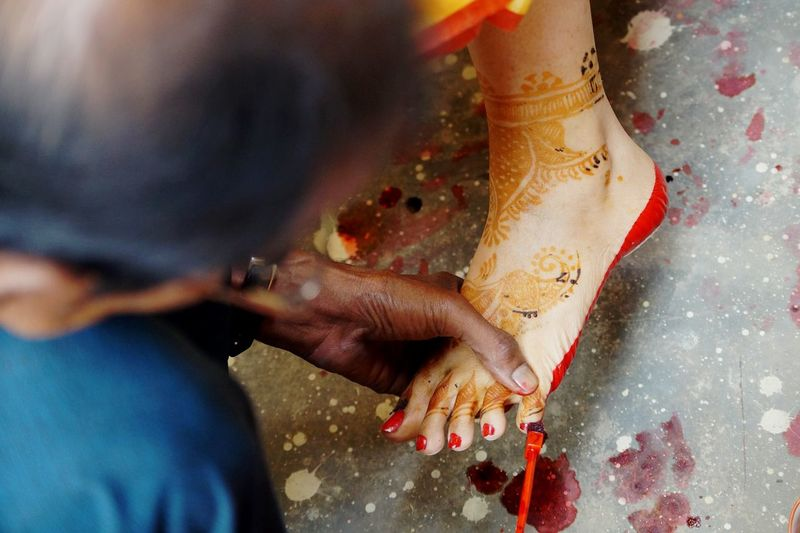 Close-up of woman applying red nail polish to bride