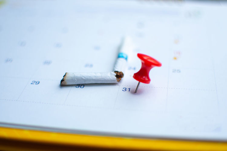 World Tobacco Day Cigarette  Close-up Indoors  No People Selective Focus Number Still Life Paper Pencil Text Pen Education Communication High Angle View Art And Craft White Color Planning Blue Document Writing Instrument